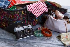 Appareil-photo près de valise avec des vêtements photo stock