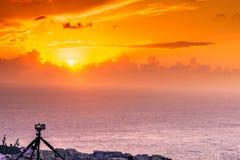 Appareil-photo prenant le film de photo du coucher du soleil au-dessus de la surface de mer Image libre de droits