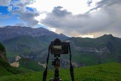 Appareil-photo sur un trépied, paysage de tir de montagne Photo stock