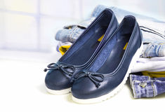 Appareillez les chaussures plates de style femelle de sport sur le fond de vêtements de jeans Photo libre de droits
