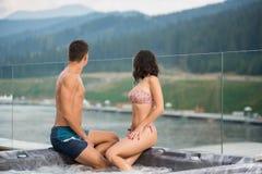 Appareillez se reposer sur le jacuzzi abaissé des pieds dans l'eau et regardez le paysage de la nature tourné à partir de l'appar image libre de droits