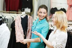 Apparel, clothing shopping. Young woman choosing dress or wear in store. Woman apparel, dress or clothing shopping. Two young women choosing wear in store Royalty Free Stock Photography