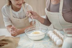 Apparence expérimentée de femme comment malaxer la pâte pour l'enfant Photographie stock libre de droits