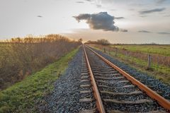 Apparently endless long single rail tracks at sunset stock images