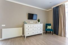 Appartamenti piani del sottotetto interno del corridoio di Luxure con il cassettone della sedia e la TV fotografia stock libera da diritti