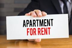 Appartamento per affitto, il messaggio sulla carta bianca e la tenuta vicino Fotografia Stock Libera da Diritti