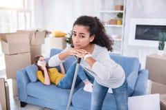 Appartement bouclé triste de nettoyage de fille tandis que compagnon de chambre étant paresseux Image stock