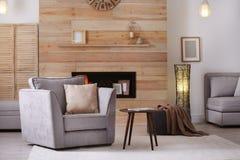 Appartement meublé confortable avec le créneau dans le mur et le fauteuil en bois image stock