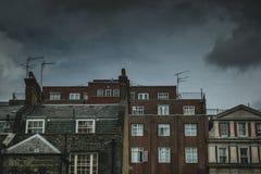 Appartements de brique se tenant contre un ciel sombre photos libres de droits