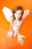 Appealing Angel. Redheaded teenage girl with white outfit and angel wings. Serious expression. Arms outstretched, palms up. Taken in studio with orange stock photo
