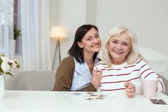 Appealing elder woman and caregiver compiling puzzle Stock Photo