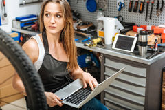 Appealing female mechanic using the laptop in the workshop Royalty Free Stock Photos