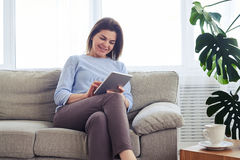 Appealing female working in laptop while sitting on sofa Royalty Free Stock Photos