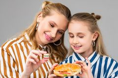 Appealing good-looking positive girls comparing different sizes of burgers. Showing smaller version. Appealing good-looking positive girls comparing different stock images