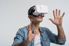 Appealing jolly man  estimating work of VR  goggles. Strange object. Happy vigorous amazed man  smiling on the isolated background while looking through VR Stock Image