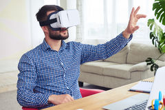 Appealing male in VR glasses orienting in space sitting at table Stock Photos