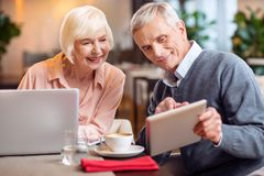 Appealing mature couple estimating technology. What opportunities. Optimistic good looking mature couple using gadgets and looking at tablet while men holding it Royalty Free Stock Photography