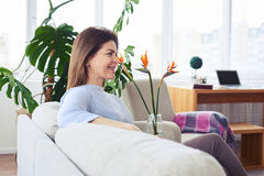Appealing mature woman sitting on sofa in bright living room Stock Photos
