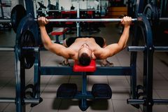 Appealing men with a naked muscular torso on a bench press using a barbell on a blurred dark background. Stock Photos