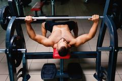 Appealing men with a naked muscular torso on a bench press using a barbell on a blurred dark background. Stock Photo