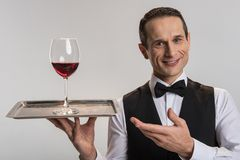 Appealing merry male waiter serving wine. Your order. Jolly glad  male waiter pointing at salver while looking at the camera and smiling Stock Photography