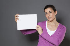 Appealing 30s woman making an announcement in holding a white insert in front of her Stock Images