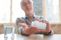 Appealing senior man consuming medication. Prescribed medication. Selective focus of senior male hands holding bottle while man putting pills in hand and glass Royalty Free Stock Photo