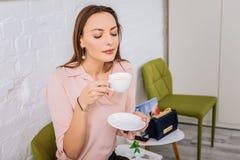 Appealing stylish businesswoman enjoying cup of fresh tasty coffee stock image