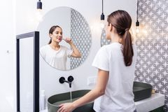 Free Appealing Woman Brushing Teeth Standing In The Bathroom Royalty Free Stock Images - 143338889