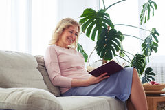 Appealing woman enjoying reading book seating on sofa Royalty Free Stock Photography