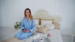 Women Caught Cold and Treated With Medication and Sitting on Large Bed in. Appealing Woman Unwell, Suffering From Cold and in Pharmacy Herb Spray to Improve Royalty Free Stock Photo