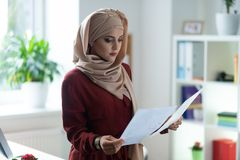 Appealing woman wearing hijab reading important documents. Important documents. Appealing woman wearing hijab reading important documents while working stock images