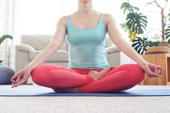 Appealing young woman being in lotus posture while sitting on yo Stock Image
