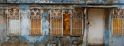 Appearance of the facade of an abandoned building with decorative bars on the windows, unrecognizable structure. House stock photo