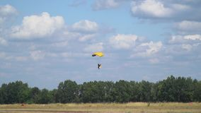 A paratrooper with the flag of Ukraine behind him on a bright parachute landing in the field against the trees in the stock footage