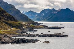 Rugged west coast of Norway`s Vesterålen Islands. Appearing as a thin line between the Atlantic Ocean and jagged mountains, a lonely road serves this remote royalty free stock image