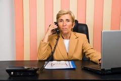 Appel aîné de femme d'affaires par le téléphone Photographie stock libre de droits