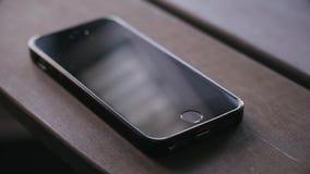 Appel d'arrivée au téléphone intelligent noir sur la table en bois Réponse d'un appel d'arrivée au téléphone intelligent banque de vidéos
