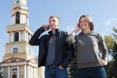 Appel d'homme et de femme par le téléphone portable Images stock