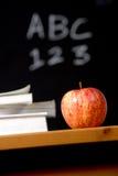 Appel en stapel boeken in klaslokaal Stock Afbeelding