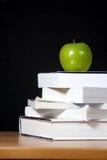 Appel op stapel boeken in klaslokaal Stock Afbeelding