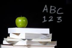 Appel op stapel boeken in klaslokaal Royalty-vrije Stock Afbeeldingen
