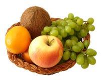 Appel, sinaasappel, kokosnoot en druiven in mand op witte achtergrond Stock Foto