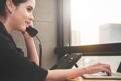 Appel téléphonique de réponse de jeune femme d'affaires image libre de droits
