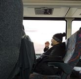 Appel téléphonique tout en montant l'autobus, banlieusard parlant à un téléphone portable, New Jersey, Etats-Unis photographie stock libre de droits