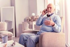 Appel téléphonique urgent de réponse supérieur aux cheveux gris rangé images libres de droits