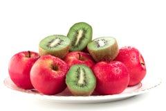 Appelen en kiwi op een schotel stock afbeeldingen