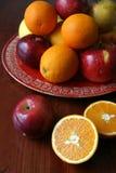 Appelen en sinaasappelen op een rode plaat Stock Foto's