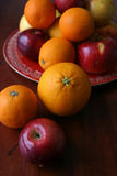 Appelen en sinaasappelen op een rode plaat Stock Afbeeldingen