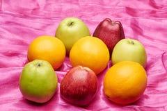 Appelen en sinaasappelen op rode doek Royalty-vrije Stock Afbeeldingen